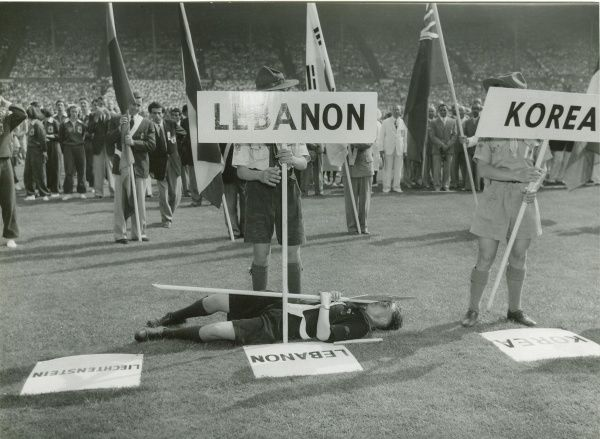 Scout collapsed through heat exhaustion whilst holding a Liechtenstein nationality sign at the 1948 London Olympics held at Wembley Stadium