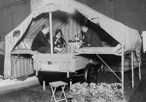 Two men and a woman trying out the facilities of a folding caravan. Date: early 1930s