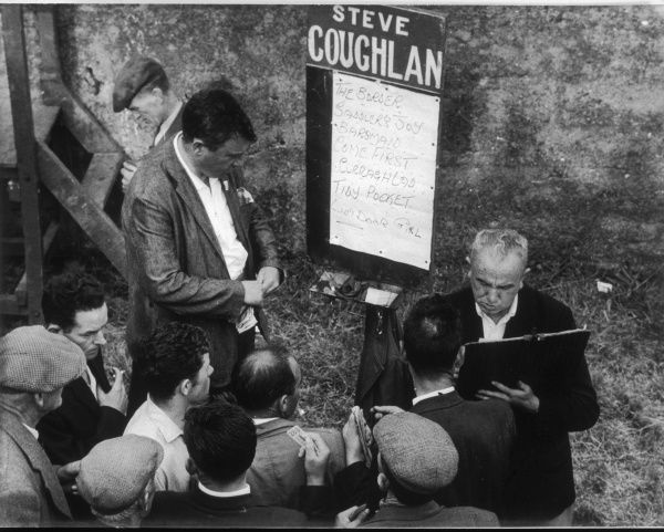 Punters collect their winnings from a bookmaker at Dingle racecourse, County Kerry, Ireland