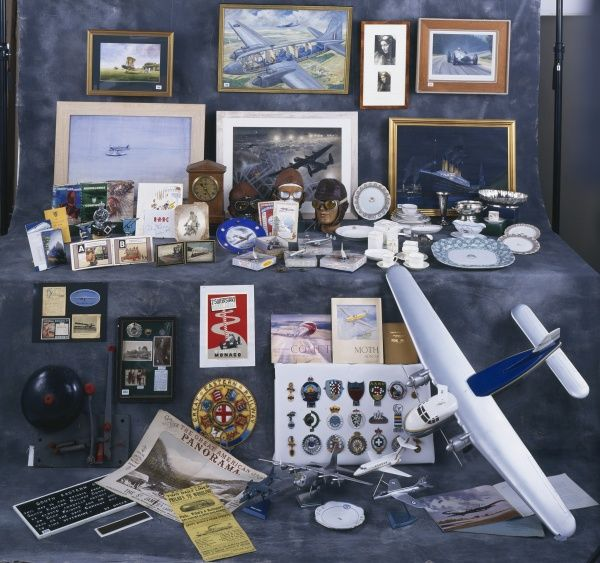 A display of memorabilia and artworks, including model aircraft, a Great Eastern Railway plaque, flying or driving goggles and leather hats, and books and prints