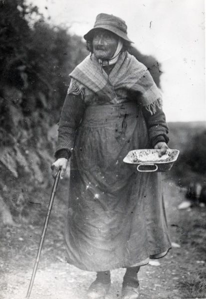 The elderly widow of a miner from Hook Colliery, near Haverfordwest, Pembrokeshire, South Wales. She is walking along a lane with the aid of a stick, and carries a tin tray in her hand