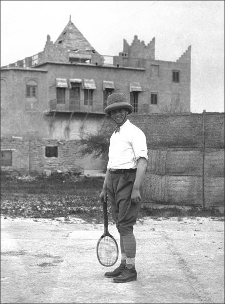 A colonial gentleman standing in a hard tennis court, Bushire (Bushehr), on the south west coast of Iran. At the time of this photograph the city had been under British occupation for five years. Photograph by Ralph Ponsonby Watts