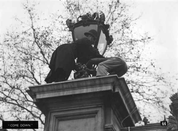 An overly enthusiastic spectator at the royal wedding of Princess Elizabeth (Queen Elizabeth II) and Prince Philip, Duke of Edinburgh on 20 November 1947, is grappled by a policeman on a plinth he's climbed onto for a better view