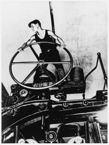 A young man, the ideal of the heroic communist worker, working at a complicated piece of machinery in a cellulose paper factory in Balakhna, Russia