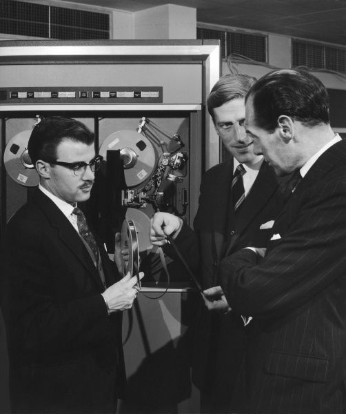 Three men examine a tape storgae device for a large industrial computer system. Photograph by Heinz Zinram
