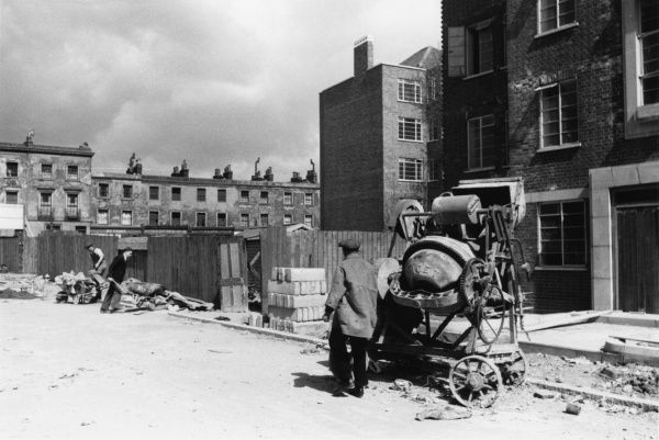 Scene outside the newly constructed Townshend Court, a new block of flats in St John's Wood, London, with older terraced housing in the background. A man operates a concrete mixer