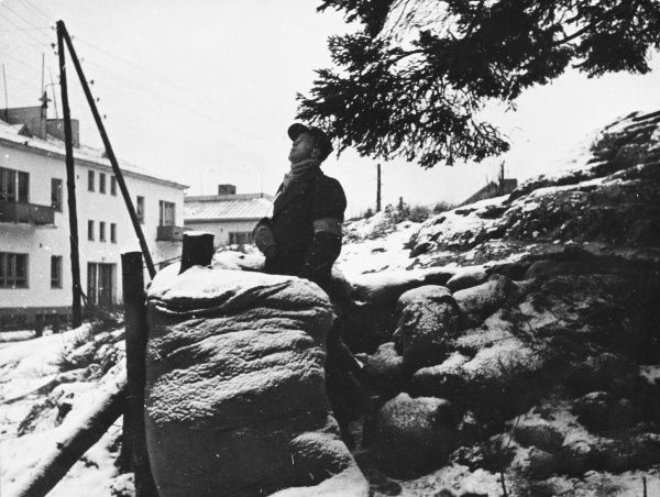 Converted and barricaded sauna baths become a first aid post where a soldier keeps watch for enemy aircraft in Helsinki, Finland during World War II