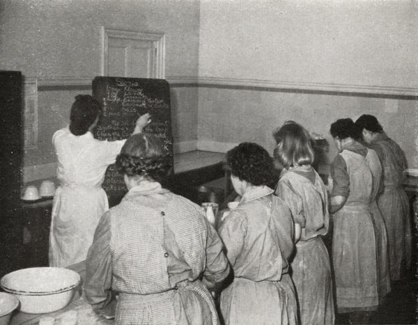 Inmates at Askham Grange female training prison in North Yorkshire take part in a cookery lesson. The instructor has written a recipe for scones on the blackboard. Date: circa 1945