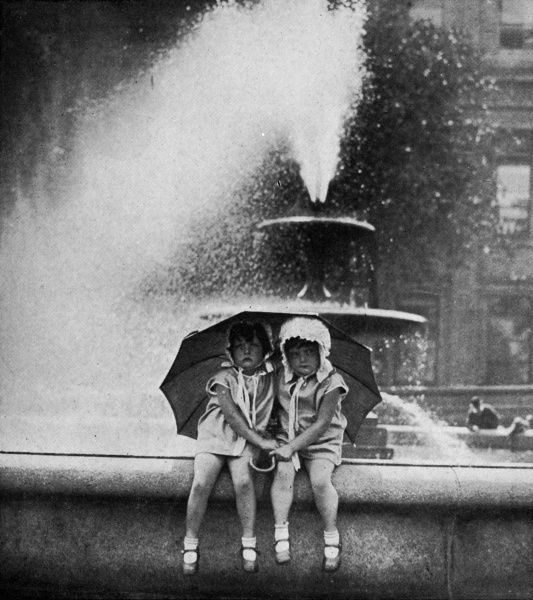 Two little girls cool off during a heat in the fountains of Trafalgar Square. Date: 1929