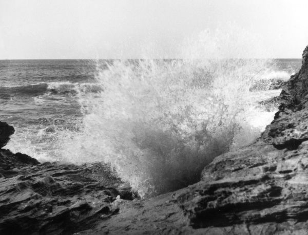 Waves crashing against the rugged coast of Cornwall, England. Date: 1960s