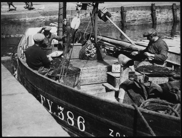 A corner of the harbour of the typical Cornish fishing village of Mevagissey, England, showing fishermen repairing their nets in preparation for the next tide