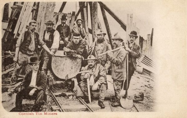 A group of Cornish Tin Miners standing around a wagon of the narrow gauge railway which served this pit. Date: circa 1903
