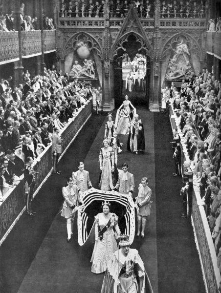 Queen Elizabeth, the Queen Mother passes along the nave of Westminster Abbey en route from the Annexe for the Coronation of her daughter, Queen Elizabeth II in June 1953. She is followed by Princess Margaret and her retinue. Date: 1953