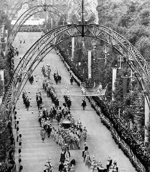 The golden State coach passing under the the great arches and golden crowns decorating the Mall, London during the procession to Westminster Abbey for the Coronation of Queen Elizabeth II in June 1953. Date: 1953