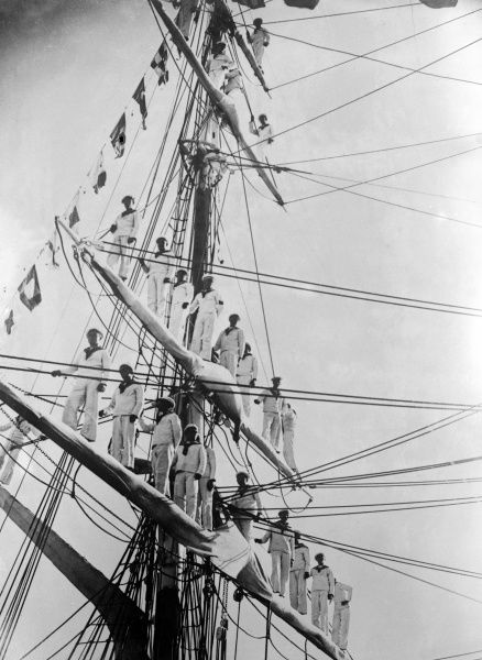 Roumanian sailors among the bunting in the rigging of a sailing ship, decorated for the Coronation of King Carol II. Date: 1930