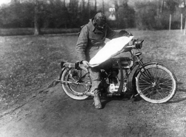 Corporal Newsham, a British Press despatch rider, studying a map on his motorcycle at Rollancourt in northern France during the First World War. Date: 1917
