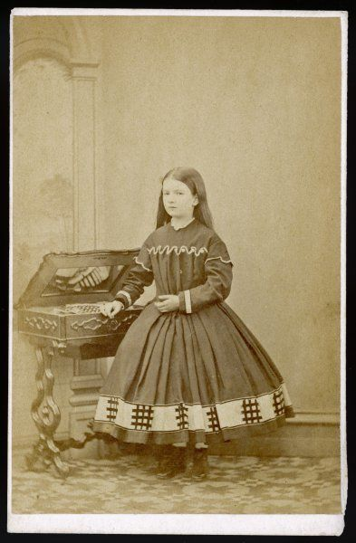 Girl wears a dress with loose, pleated bodice, a crinoline supported short skirt trimmed with lattice motifs & sleeves with epaulettes & turned back cuffs. Hair worn plain