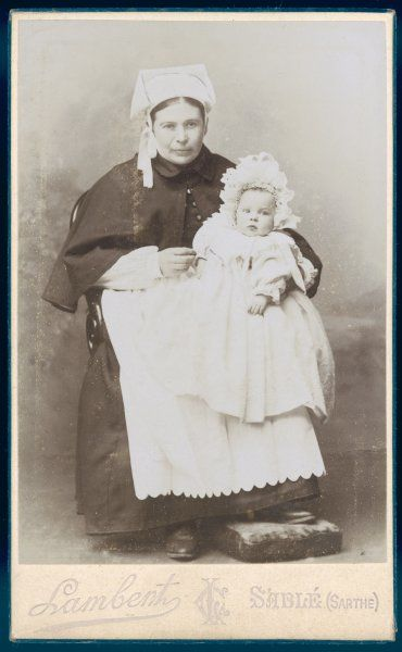 A baby in long clothes & an elaborate high lacy bonnet has its photograph taken with its nurse maid who wears a short cape, square shaped headgear & apron with a scalloped edge