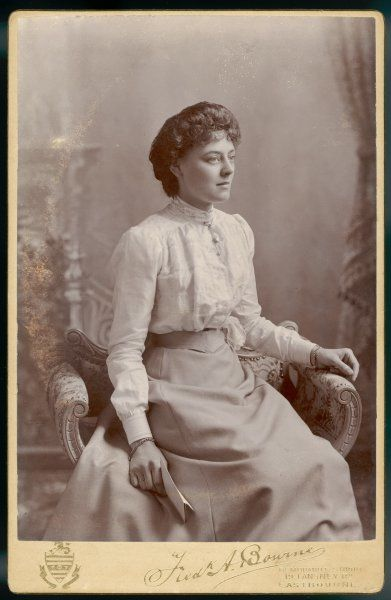 A young woman wears a plain gored skirt & a blouse trimmed with lace with an all-round collar of a sensible height. A 'V' shaped belt emphasizes her small waist
