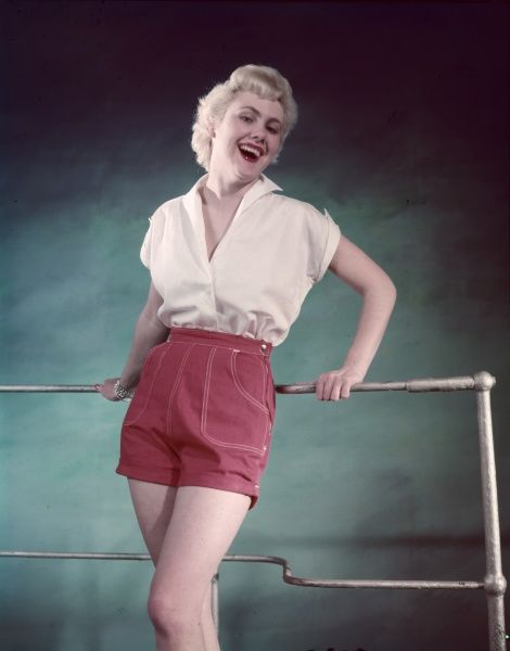Carefree fifties blonde, wearing a cap sleeve blouse & red shorts with side fastening, patch pockets & white over-stitching, leans against some railings