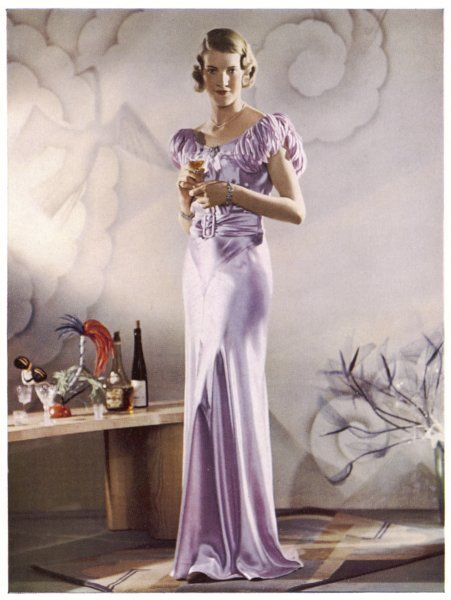 Lilac satin bias cut gown with gathered self-coloured belt, gored skirt & marabou trimmed shoulder straps. Her blonde hair is dressed in a marcel wave