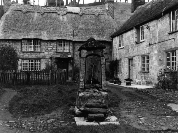 A picturesque corner of Shaftesbury, Dorset, England, showing the courtyard of some old cottages and the fine old pump. Date: 1950s
