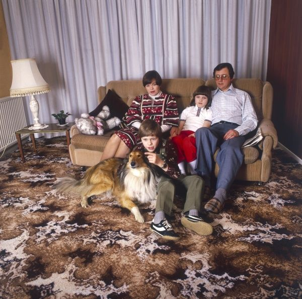 A lazy family of 'Couch Potatoes', lounging on the sofa together watching TV with their happy dog and obligatory swirly carpet! Date: 1981