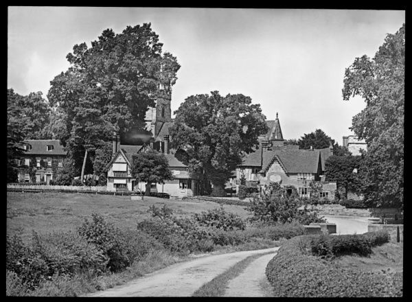 View of a church and houses, at the end of a winding country lane