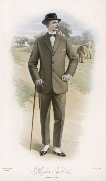 A tweed lounge suit consisting of a lounging jacket & narrow fit trousers with turn-ups & a crease, worn with spats, a bowtie & a felt hat