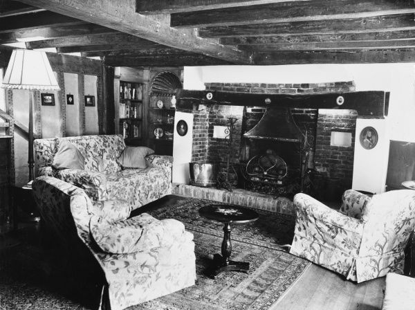 The interior of an English cottage, with exposed beams on the ceiling and an inglenook fireplace. Date: 1960s
