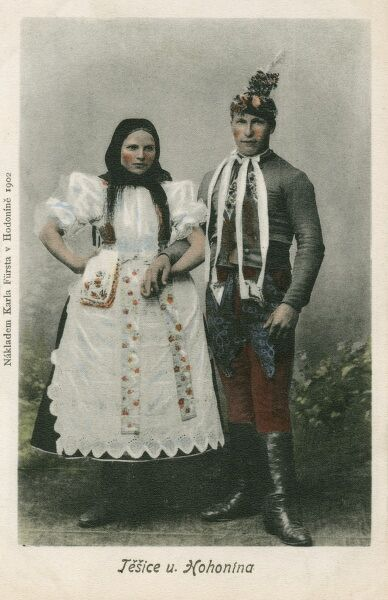 A couple from Hodonin on the River Morava, in the southeast of Moravia, in the Czech Republic. They stand arm in arm, both wearing traditional local costume. Perhaps they are newlyweds?
