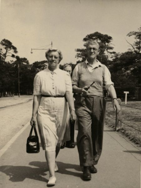 A couple on holiday, photographed as they walk along.  circa 1960s