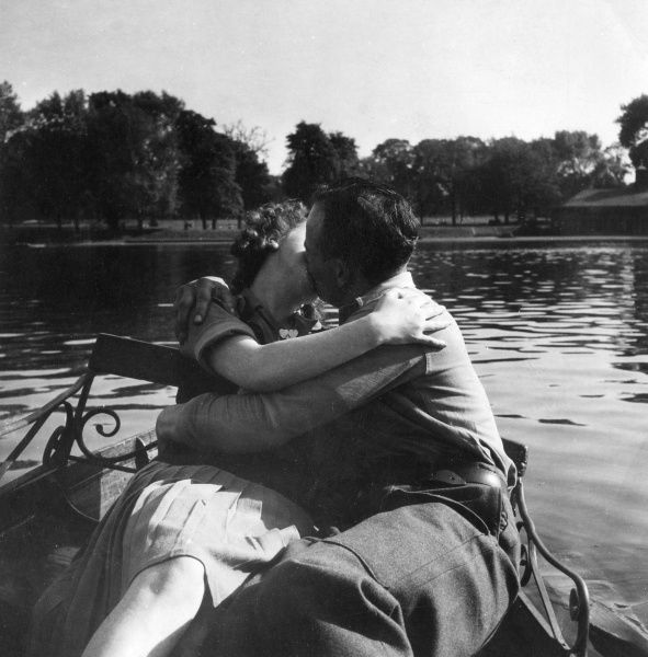 A couple get lost in a kiss while rowing a boat on a lake in a park, probably the Serpentine in Hyde Park, London. 1940s