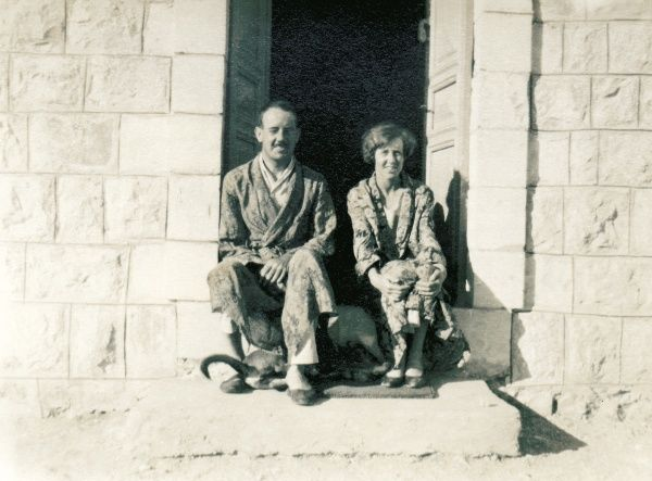 A couple in pyjamas and dressing gowns sitting on a stone step in the bright sunshine