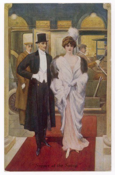 He: long black coat with velvet collar, top hat, white waistcoat, wing collar & tie. She: pink gown, white fur coat with silver fox fur stole, bandeau & plume headdress