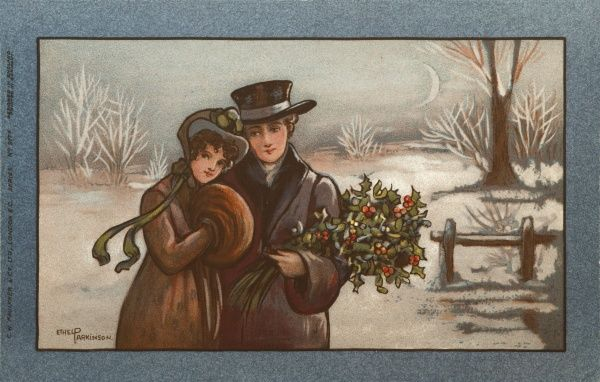 A young couple in a snowy landscape, dressed in 19th century style. She is wearing a fur coat and is keeping her hands warm in a fur muff. He is carrying a large bunch of holly