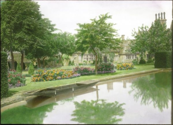 View of Court Farm (unidentified location) and garden, with a large pond, grass, trees and flowerbeds