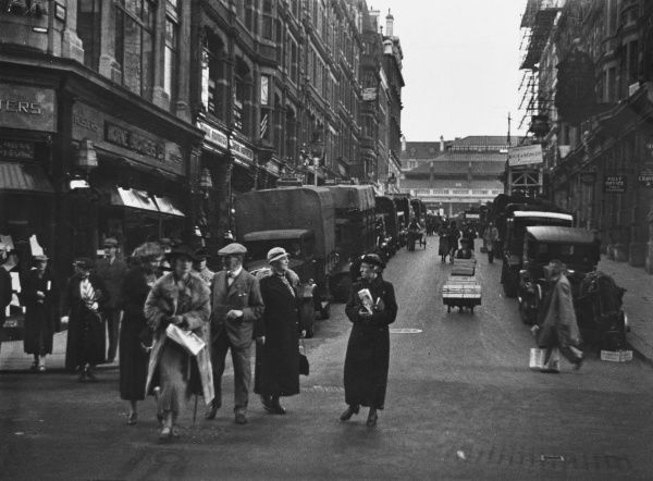 Busy scene in central London, looking towards Covent Garden, showing parked cars and vans unloading for the market and well-dressed people in hats milling about