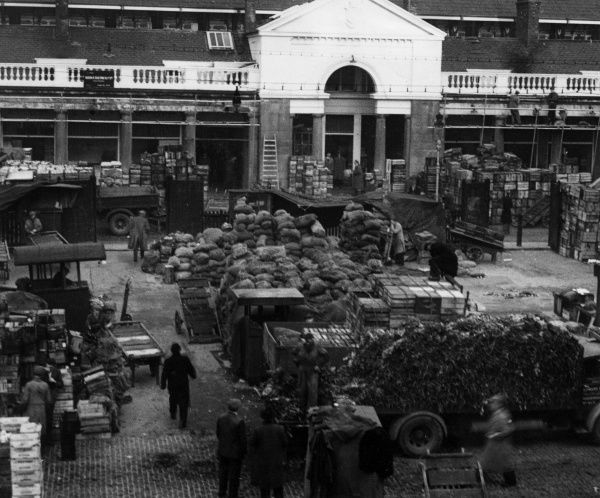 COVENT GARDEN A view of the market setting up early in the morning with piles of crates and sacks lying around. Date: Spring, circa 1930