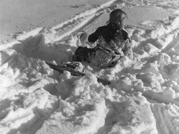 Oops! This little girl has fallen whilst out skiing and ended up rolling in the snow! Date: 1930s
