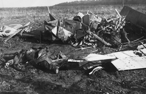 A crashed British single-seat fighter plane with a dead airman lying on the ground beside it, on the Siegfried Line in northern France during the First World War. Date: May-August 1917