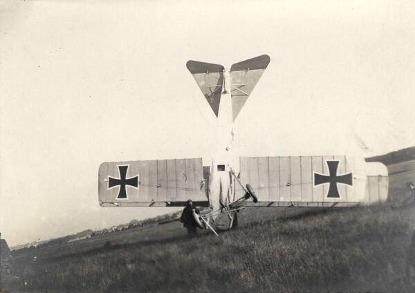 A german light biplane which has crash landed and come to rest on its nose on the battlefield - World War One
