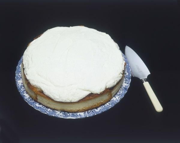 A home-made cream cake, with a cake slice beside it. Date: 1980