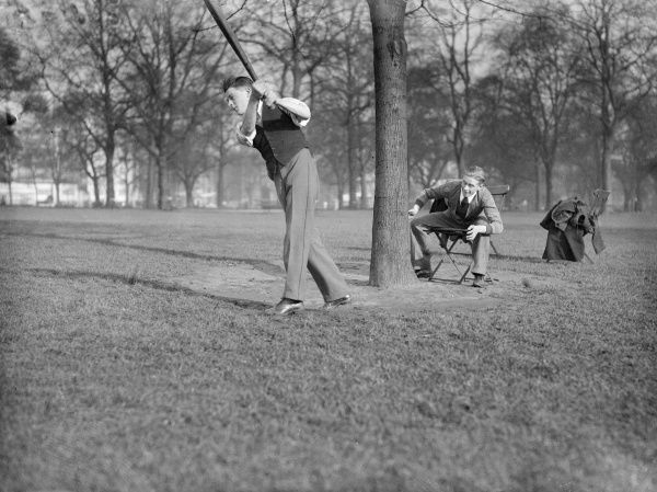 A game of cricket in a London park, the wicket keeper sitting on a chair behind the 'wicket' tree! Date: early 1930s