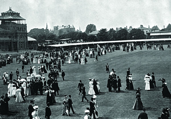 An elegant crowd milling around during a cricket match between Eton and Harrow schools