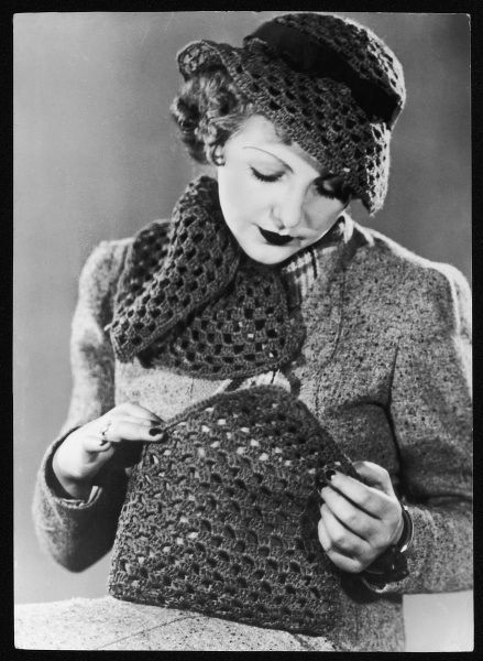A woman looks in her bag, crocheted from red rust wool; her hat and scarf are also crocheted and look smart against her fawn tweed coat