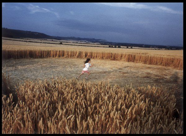 Alton Barnes, Wiltshire : a small girl runs across the largest circle in the formation, demonstrating its huge size
