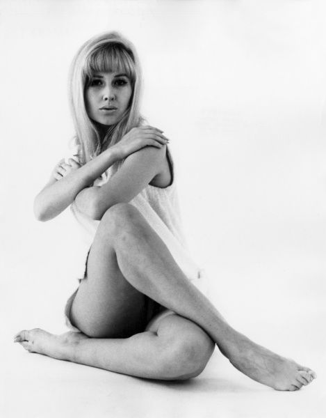 A blonde model strikes a provocative cross-legged pose. Date: 1960s