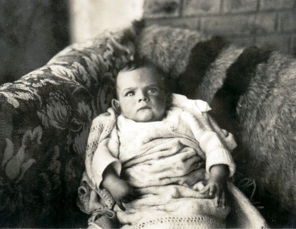 A cross looking baby lying on a sofa