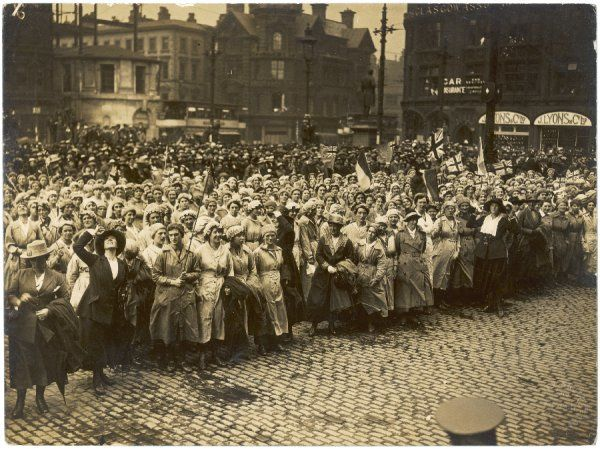 A large crowd of World War One women munitions workers gather in Manchester; several wave Union Jack flags